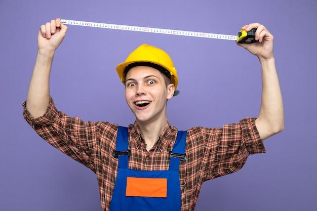 Jonge mannelijke bouwer draagt uniform uitrekkende meetlint geïsoleerd op paarse muur