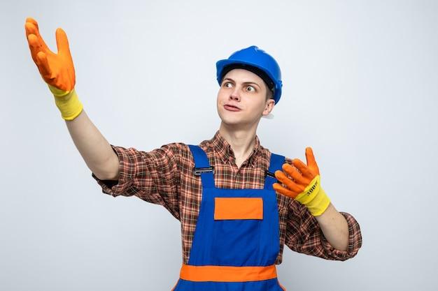 Jonge mannelijke bouwer dragen uniform met handschoenen geïsoleerd op een witte muur