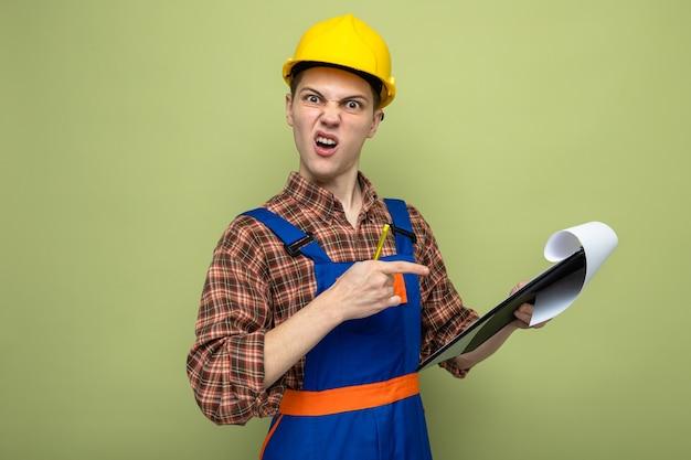 Jonge mannelijke bouwer houdt vast en wijst naar klembord in uniform geïsoleerd op olijfgroene muur
