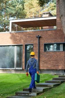 Jonge mannelijke bouwer in blauwe overall met gereedschapskist op de bouwplaats van een huisje