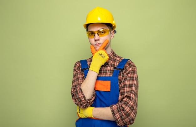 Jonge mannelijke bouwer met uniform en handschoenen met bril geïsoleerd op olijfgroene muur