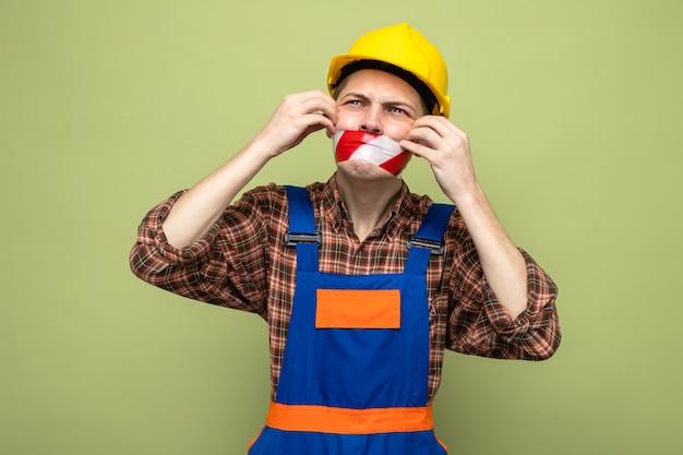 Jonge mannelijke bouwer met uniforme verzegelde mond met ducttape geïsoleerd op olijfgroene muur