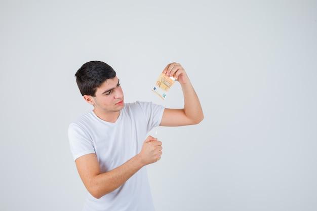 Jonge mannelijke brandende eurobankbiljet close-up in t-shirt en op zoek vrolijk, vooraanzicht.