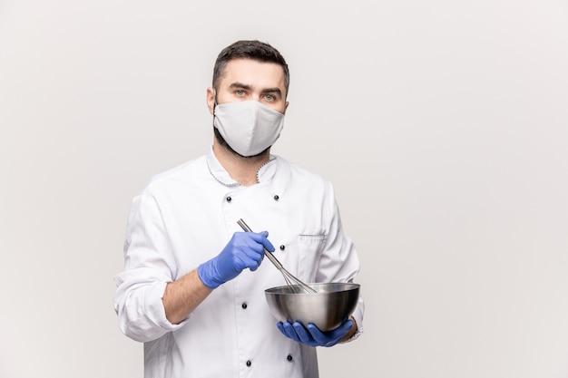 Jonge mannelijke chef-kok in uniform, beschermend masker en handschoenen die melk en rauwe eieren in metalen kom mengen tijdens het koken van voedsel voor klanten van restaurant