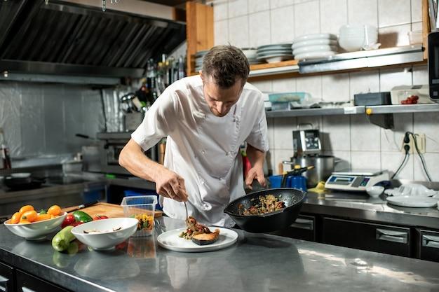 Jonge mannelijke chef-kok in uniform met koekenpan met groentestoofpot terwijl hij over tafel met bord buigt en voedsel op een stuk gebakken zalm zet