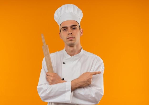 Jonge mannelijke cool dragen chef-kok uniforme kruising hand met deegroller wijst vinger naar kant op geïsoleerde gele muur met kopie ruimte