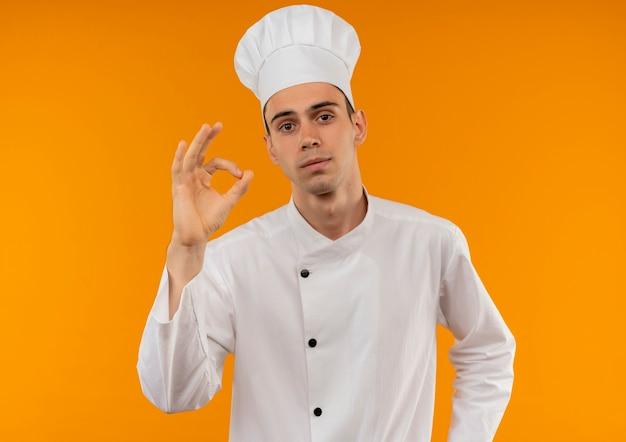 Jonge mannelijke coole dragen chef-kok uniform met ok gebaar op geïsoleerde gele muur
