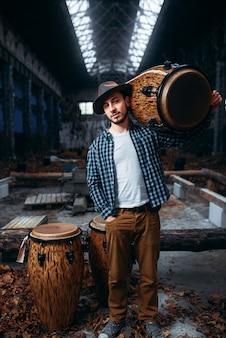Jonge mannelijke drummer houdt houten trommel op de schouder, fabriekswinkel. djembe, muzikaal percussie-instrument,