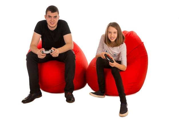 Jonge mannelijke en grappige meisje spelen van videospellen zittend op rode zitzak stoelen geïsoleerd op wit