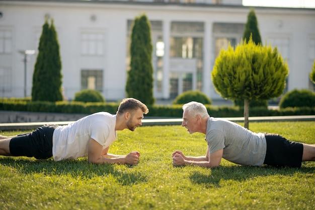 Jonge mannelijke en grijsharige man staan in plank, kijken elkaar