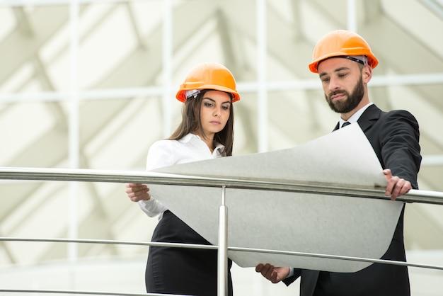 Jonge mannelijke en vrouwelijke architect in het moderne kantoor.