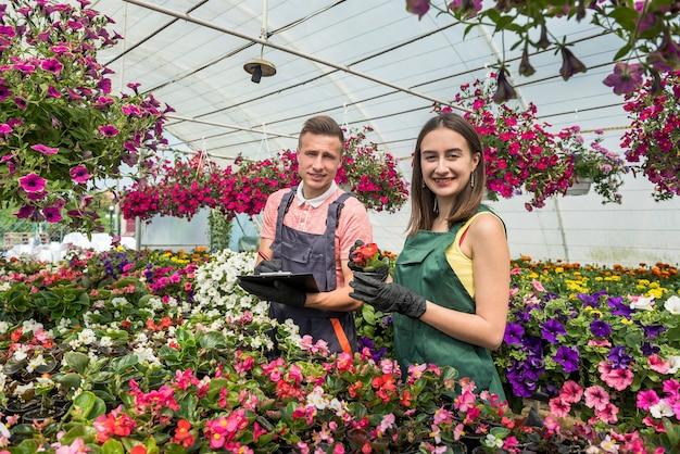 Jonge mannelijke en vrouwelijke bloemisten met klembord communiceren terwijl ze de voorraad planten in een kas analyseren.