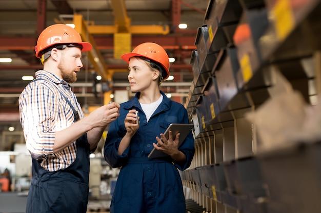 Jonge mannelijke en vrouwelijke ingenieurs in helmen en overall bespreken kwaliteit van nieuwe technische benodigdheden in werkplaats