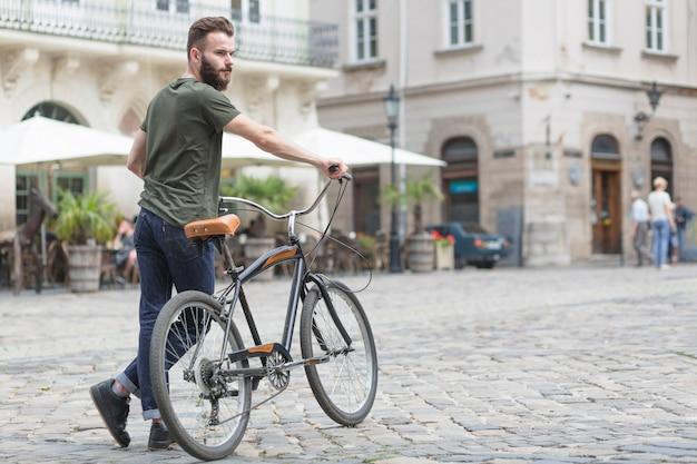 Jonge mannelijke fietser met zijn fiets op straat