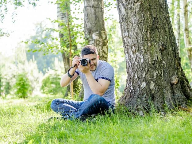Jonge mannelijke fotograaf die aard op de zomerdag fotograferen