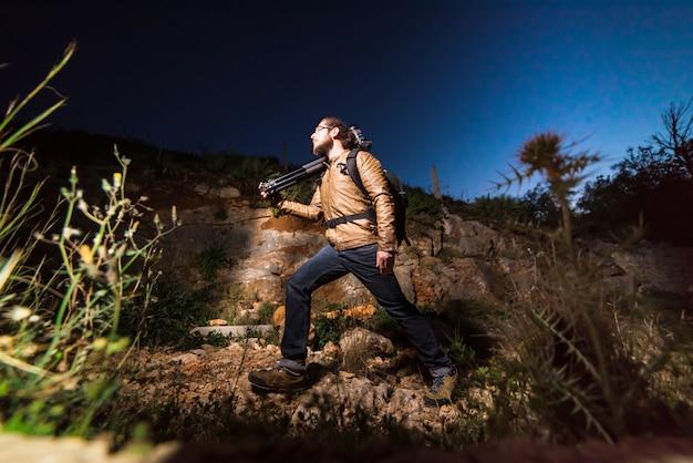 Jonge mannelijke fotograaf die op rotsstrand lopen met camera op driepoot in de avond