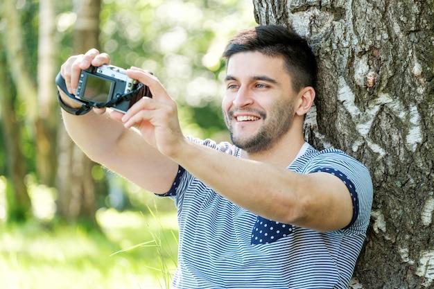 Jonge mannelijke fotograaf die selfie op de zomerdag maken