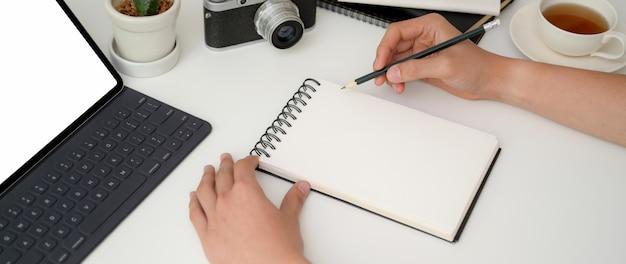 Jonge mannelijke fotograaf korte notitie over notebook