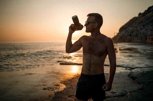 Jonge mannelijke fotograaf maakt foto's van de zee bij zonsondergang terwijl hij aan de kust staat. zee zonsondergang. selectieve aandacht. toerist fotografeert het zeegezicht