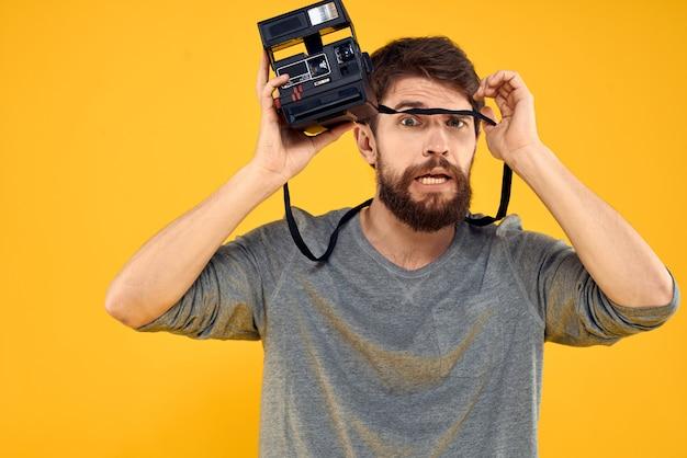 Jonge mannelijke fotograaf met een oude filmcamera in zijn handen die emotioneel stellen