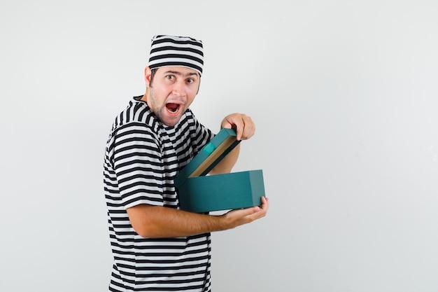 Jonge mannelijke giftdoos in t-shirt, hoed openen en nieuwsgierig kijken.
