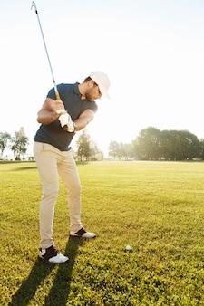 Jonge mannelijke golfspeler die bal met een club raakt