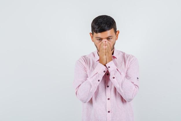 Jonge mannelijke hand in hand biddend gebaar in roze shirt en op zoek hoopvol, vooraanzicht.