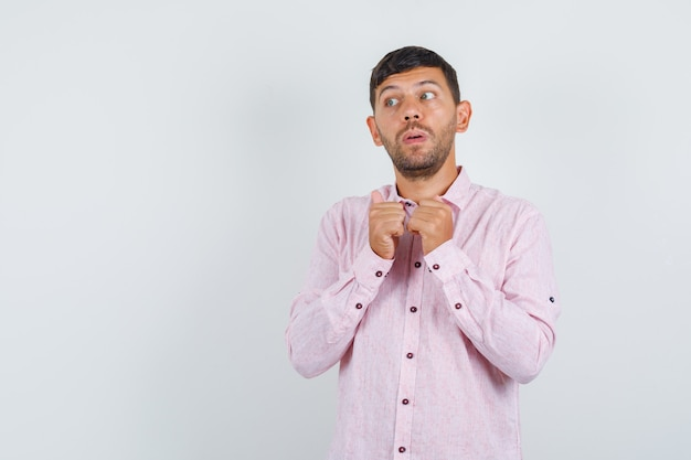 Jonge mannelijke hand in hand in de buurt van kraag in roze overhemd en twijfelachtig op zoek. vooraanzicht.