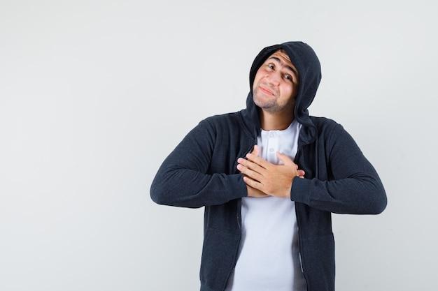 Jonge mannelijke hand in hand op de borst in t-shirt, jas en op zoek dankbaar, vooraanzicht.
