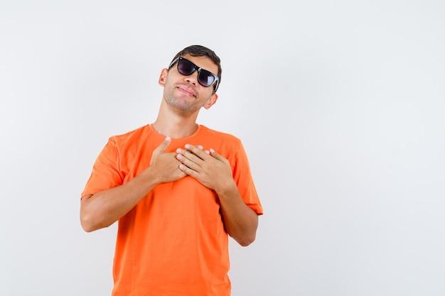 Jonge mannelijke hand in hand op hart in oranje t-shirt en vredig op zoek