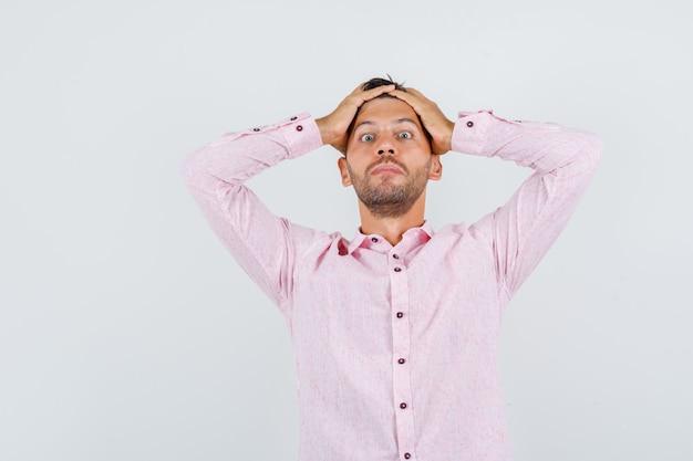 Jonge mannelijke hand in hand op het hoofd in roze shirt en uitgeput op zoek. vooraanzicht.