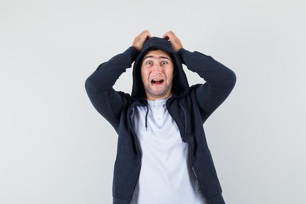 Jonge mannelijke hand in hand op het hoofd in t-shirt, jasje en op zoek weemoedig. vooraanzicht.