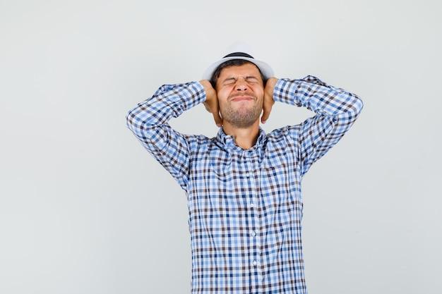 Jonge mannelijke hand in hand op oren in ingecheckte overhemd