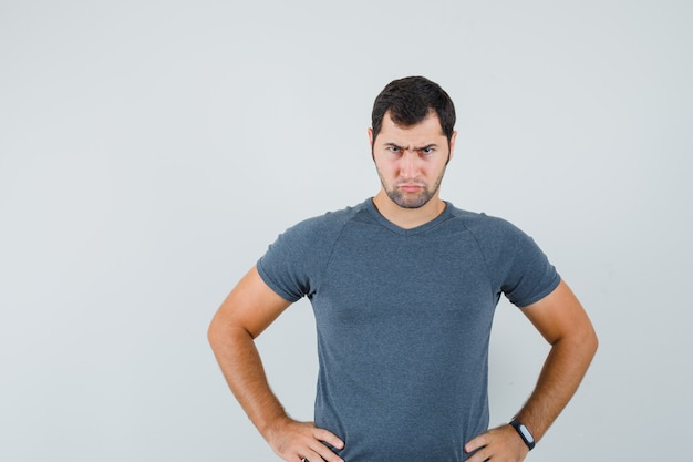 Jonge mannelijke hand in hand op taille in grijs t-shirt en op zoek naar serieus