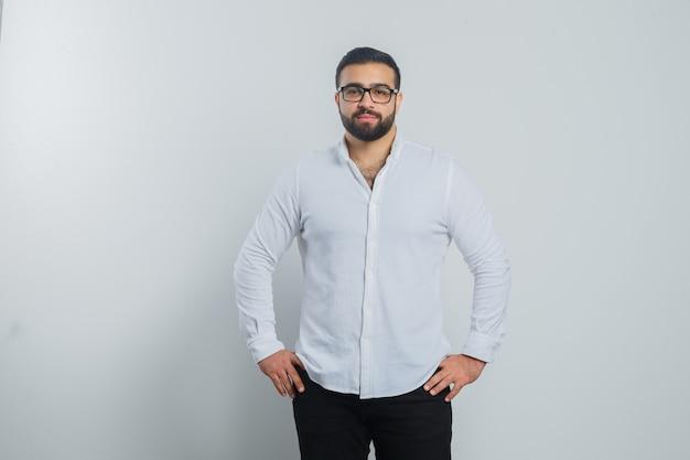 Jonge mannelijke hand in hand op taille in wit overhemd, broek en op zoek knap