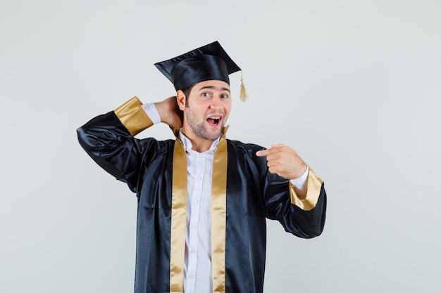 Jonge mannelijke hand op de nek, wijzend op zichzelf in afgestudeerde uniform vooraanzicht.