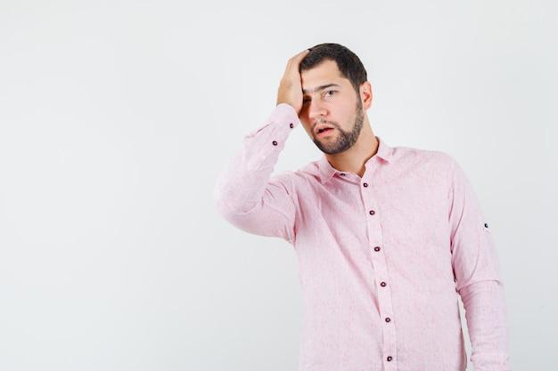 Jonge mannelijke hand op het hoofd in roze shirt en op zoek sorry