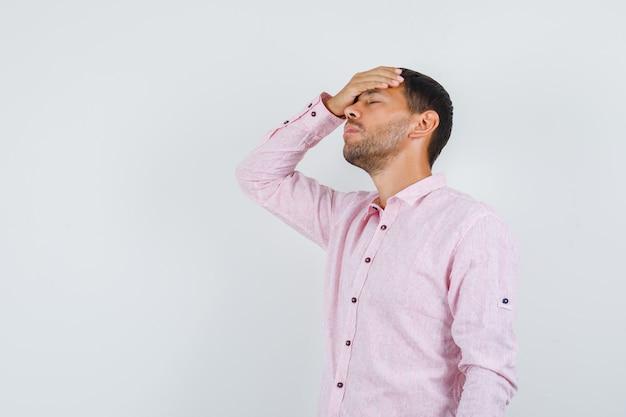 Jonge mannelijke hand op het voorhoofd in roze shirt en op zoek sorry, vooraanzicht.
