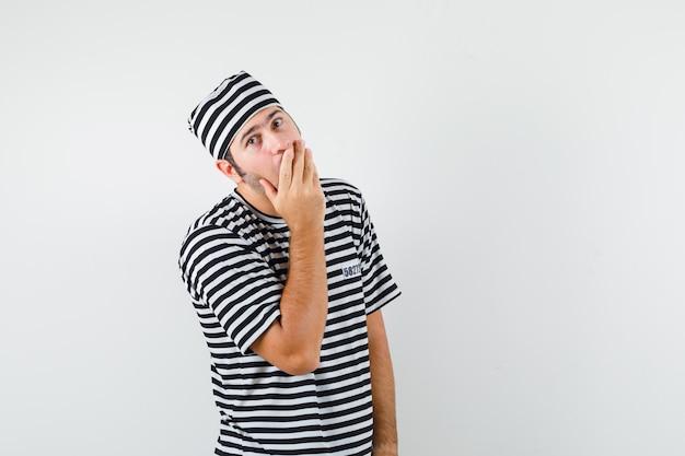 Jonge mannelijke hand op mond in t-shirt, hoed en op zoek verrast, vooraanzicht.