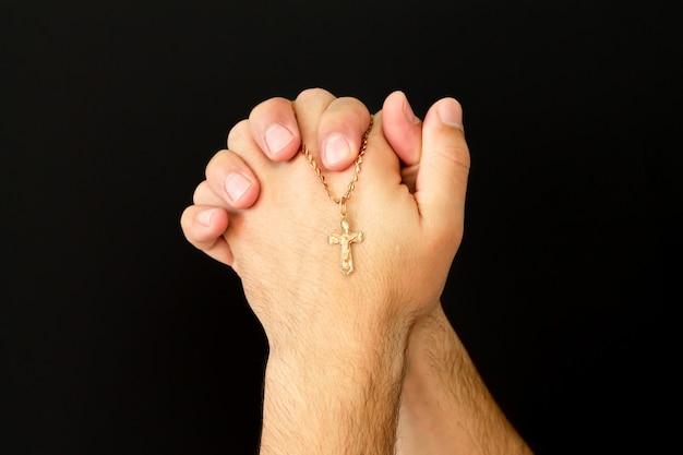Jonge mannelijke handen met christelijk kruis bidden tot god in de kerk