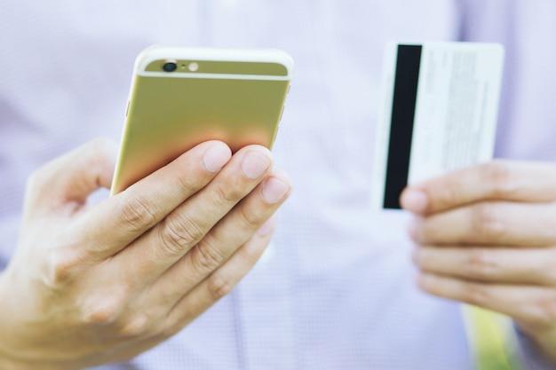 Jonge mannelijke handen met creditcard en met behulp van telefoon sit bestellen producten en zoek informatie online winkelen kopen verkopen of betalen.