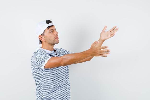 Jonge mannelijke handen uitrekken om fout in t-shirt en pet te vinden