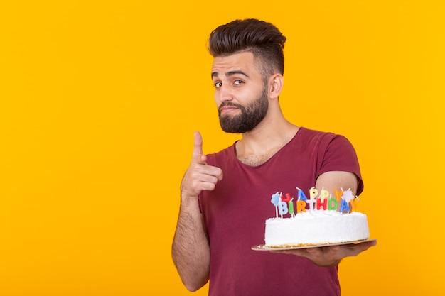 Jonge mannelijke hipster met een baard die een cake met de inscriptie gelukkige verjaardag houdt