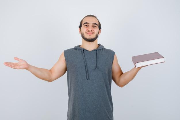 Jonge mannelijke holdingsboek terwijl het maken van schalen gebaar in mouwloze hoodie en op zoek zelfverzekerd. vooraanzicht.