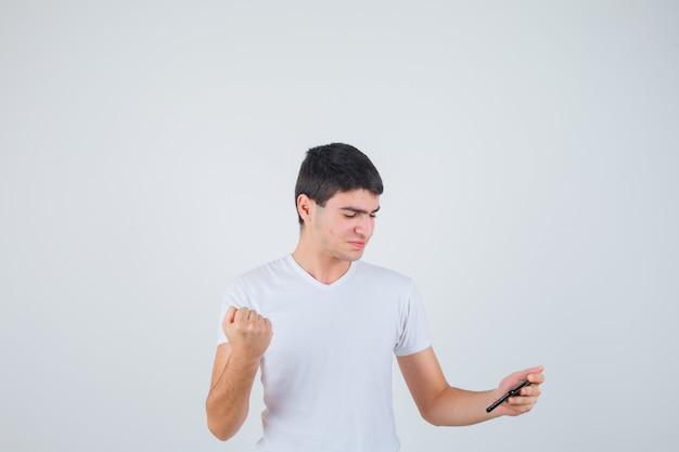 Jonge mannelijke holdingstelefoon, die gebalde vuist in t-shirt toont en vrolijk kijkt. vooraanzicht.