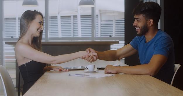 Jonge mannelijke hr-manager handenschudden gastvrije ingehuurde werknemer kreeg nieuwe baan, werkgever handen schudden feliciteren werknemer kandidaat na succesvol interview, deal sluiten met klant, contract ondertekenen.