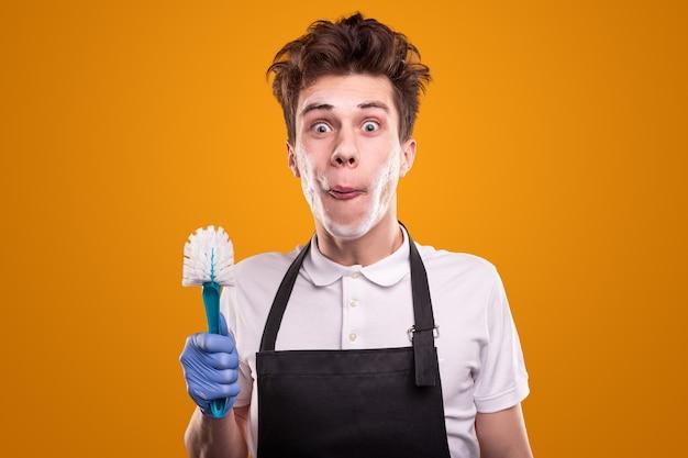 Jonge mannelijke huishoudster met toiletborstel grimassen en camera kijken tegen gele achtergrond
