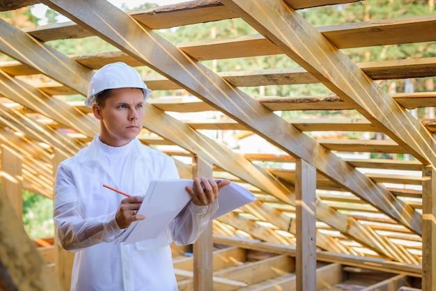 Jonge mannelijke ingenieur die bouwwerkzaamheden bekijkt