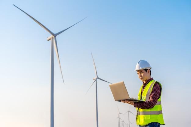 Jonge mannelijke ingenieur die met laptop computer tegen windturbineboerderij werkt