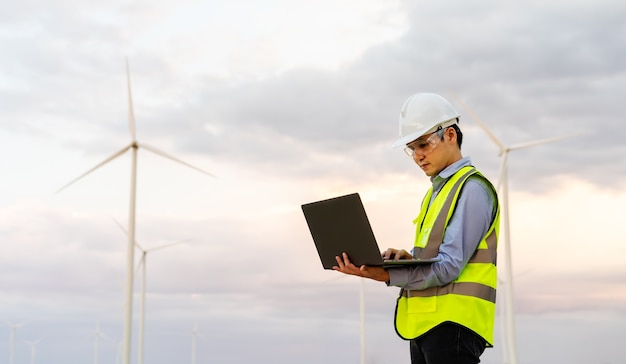 Jonge mannelijke ingenieur die met laptopcomputer werkt tegen windturbinepark